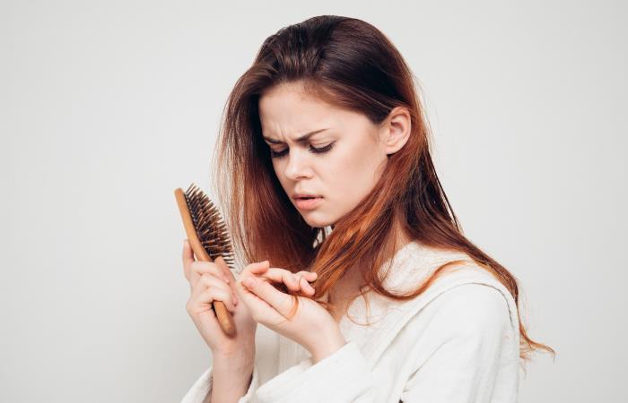 Chica con cepillo y cabello en su mano
