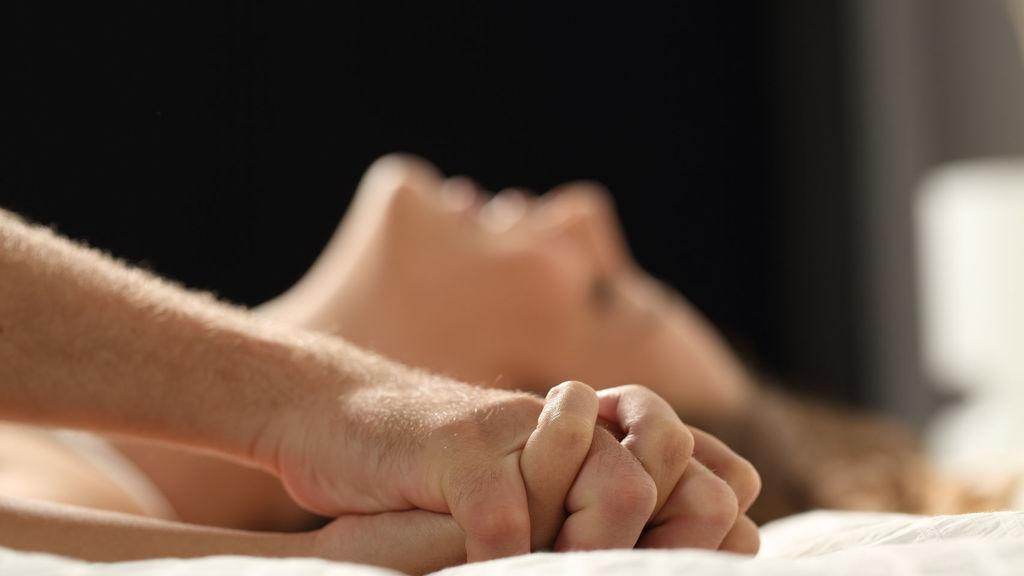 Chica con orgasmo agarrando la mano a su pareja