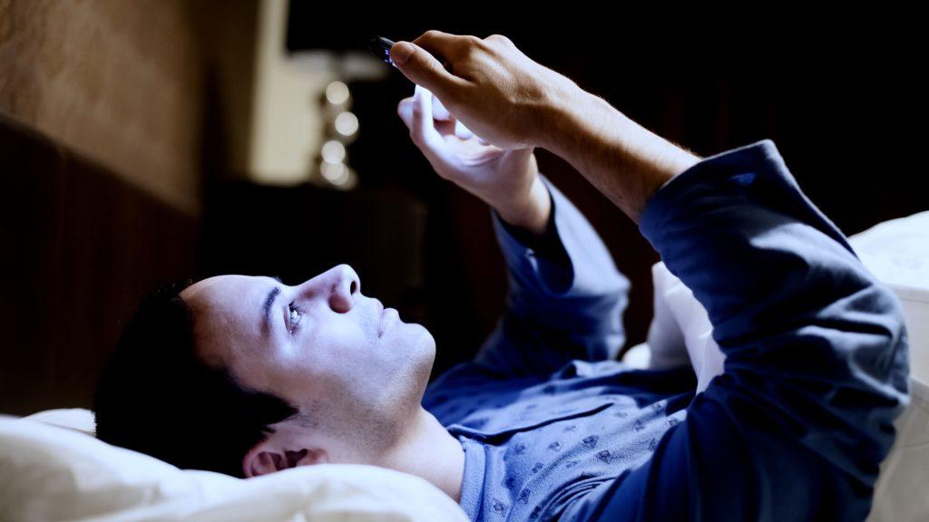 Chico apunto de dormir con celular