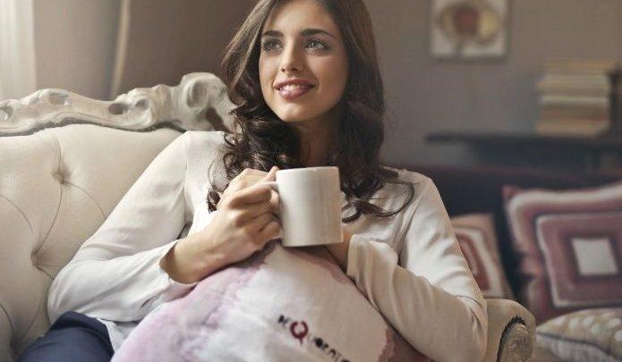 Chica sonriendo con taza en la mano