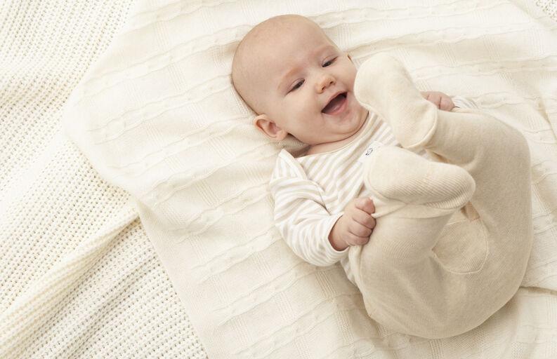 Bebé en la cama sonriendo
