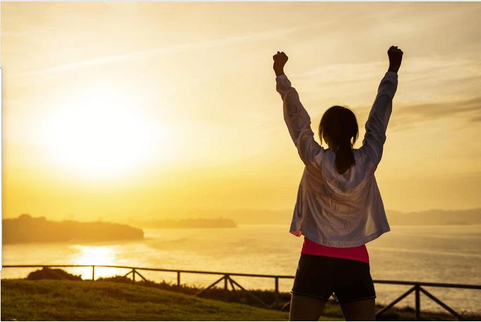 Mujer manos arriba motivada - Cómo llevar una vida saludable