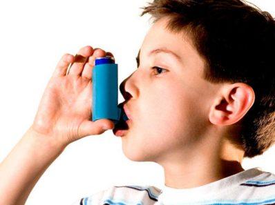 Niño con asma e inhalador