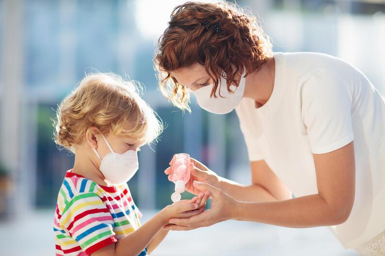 mama da gel antibacterial a su hijo - Los niños y el uso del Cubrebocas